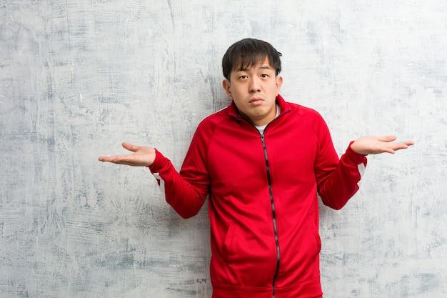 Молодые спортивные фитнес китайцы смущены и сомнительны