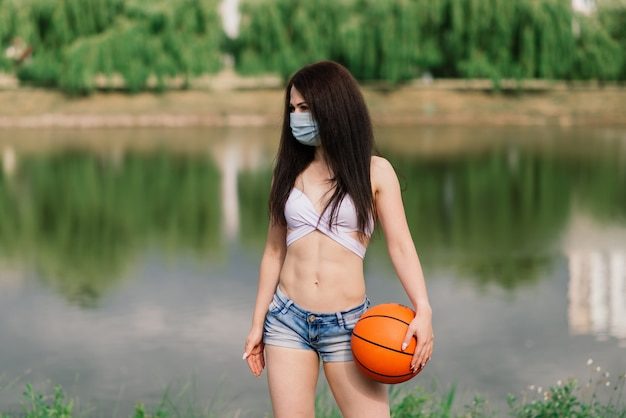 Молодой спортивный баскетболист женщины фитнеса используя маску covid для защиты с мячом, фоном озера.