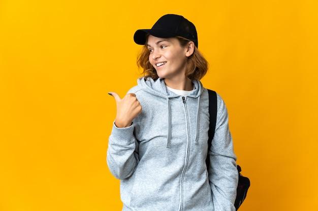 제품을 제시하기 위해 측면을 가리키는 외진 배경 위에 스포츠 가방을 든 젊은 스포츠 그루지야 여성