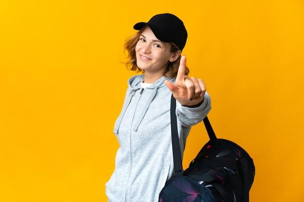 젊은 스포츠 그루지야 어 여자 격리 된 배경 위에 스포츠 가방을 보여주는 손가락을 들어 올려