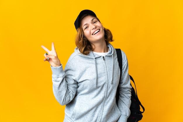 笑顔と勝利の兆候を示す孤立した背景の上のスポーツバッグを持つ若いスポーツジョージア女性