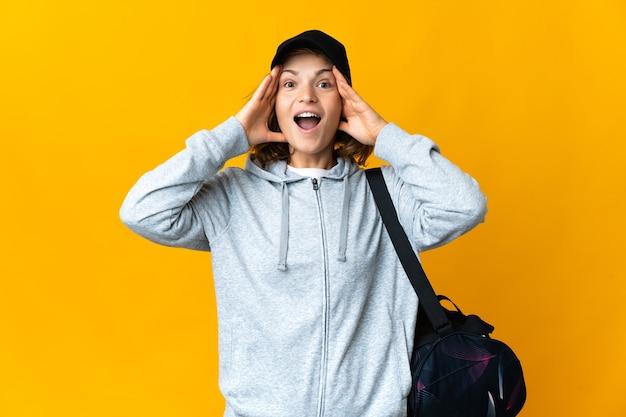 Молодая спортивная грузинка со спортивной сумкой на изолированном фоне с удивленным выражением лица
