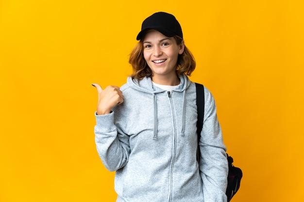 제품을 제시하기 위해 측면을 가리키는 격리 된 벽 위에 스포츠 가방을 가진 젊은 스포츠 그루지야 여자