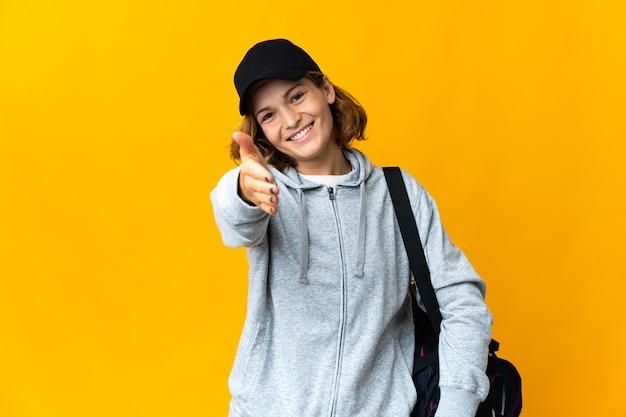 Молодая спортивная грузинка со спортивной сумкой над изолированной стеной пожимает руку для заключения хорошей сделки