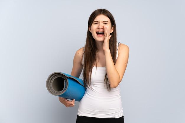 Молодая спортивная девушка идет на занятия йогой, держа циновку и крича с широко открытым ртом