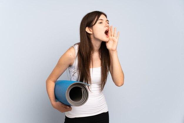 Молодая спортивная девушка идет на занятия йогой, держа циновку крича