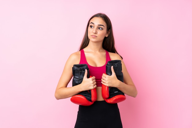 Young sport girl over isolated pink  with boxing gloves
