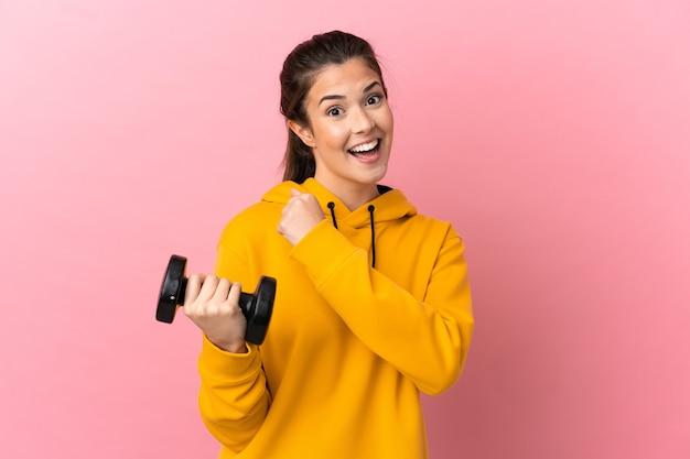 승리를 축하 격리 된 분홍색 배경 위에 역도를 만드는 젊은 스포츠 소녀