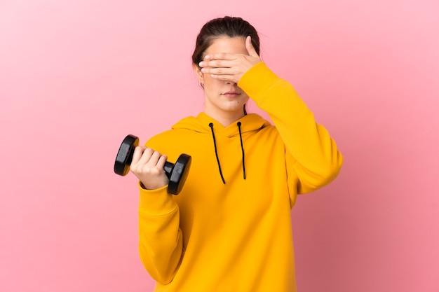 손으로 눈을 덮고 고립 된 분홍색 배경 위에 역도를 만드는 젊은 스포츠 소녀. 뭔가보고 싶지 않아