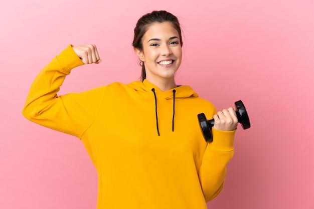 강한 제스처를 하 고 격리 된 분홍색 배경 위에 역도를 만드는 젊은 스포츠 소녀