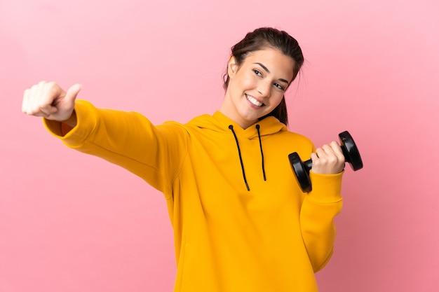 제스처를 엄지 손가락을주는 고립 된 분홍색 배경 위에 역도를 만드는 젊은 스포츠 소녀