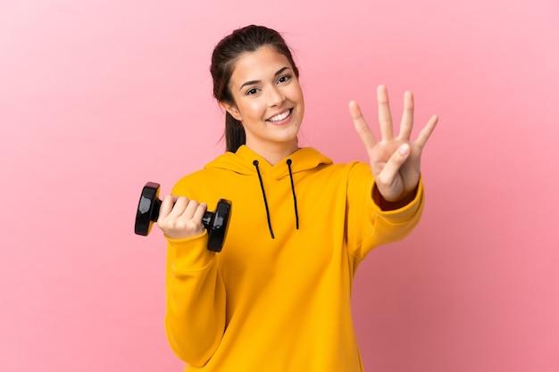 젊은 스포츠 소녀 격리 된 분홍색 배경 위에 역도 행복 하 고 손가락으로 4 세