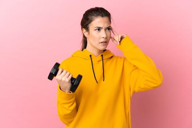 Молодая спортивная девушка делает тяжелую атлетику на изолированном розовом фоне, сомневаясь и думая