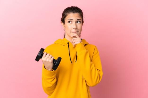 의심과 생각을 갖는 고립 된 분홍색 배경 위에 역도를 만드는 젊은 스포츠 소녀