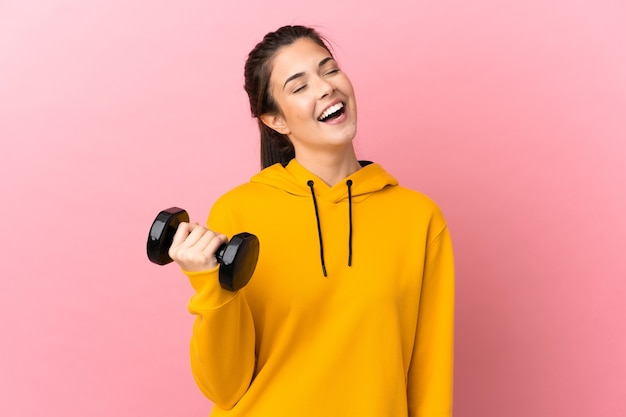 격리 된 분홍색 배경 웃음 위에 역도를 만드는 젊은 스포츠 소녀