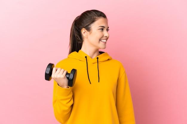 Молодая спортивная девушка делает тяжелую атлетику на изолированном розовом фоне, глядя в сторону