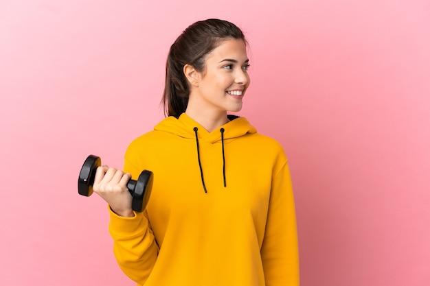 Молодая спортивная девушка делает тяжелую атлетику на изолированном розовом фоне, глядя в сторону и улыбаясь