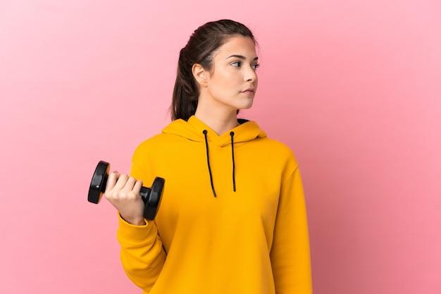 측면을 찾고 격리 된 분홍색 배경 위에 역도를 만드는 젊은 스포츠 소녀