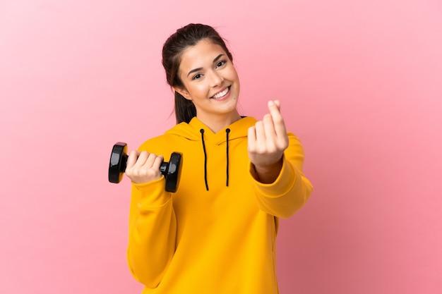 Молодая спортивная девушка делает тяжелую атлетику на изолированном розовом фоне, делая денежный жест