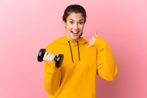 Молодая спортивная девушка делает тяжелую атлетику на изолированном розовом фоне, делая жест телефона. перезвони мне знак