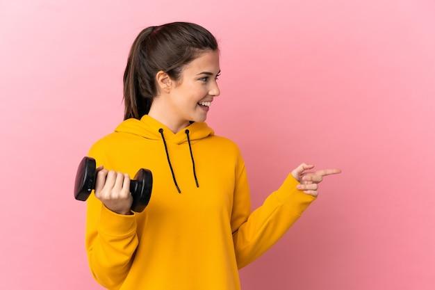 젊은 스포츠 소녀 측면에 손가락을 가리키는 격리 된 분홍색 배경 위에 역도를 만들고 제품을 제시