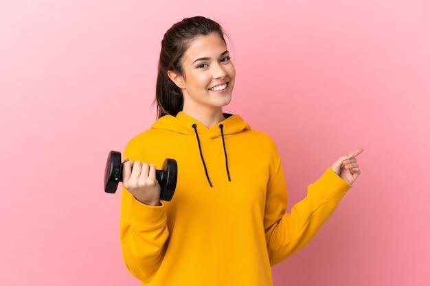측면에 손가락을 가리키는 격리 된 분홍색 배경 위에 역도를 만드는 젊은 스포츠 소녀