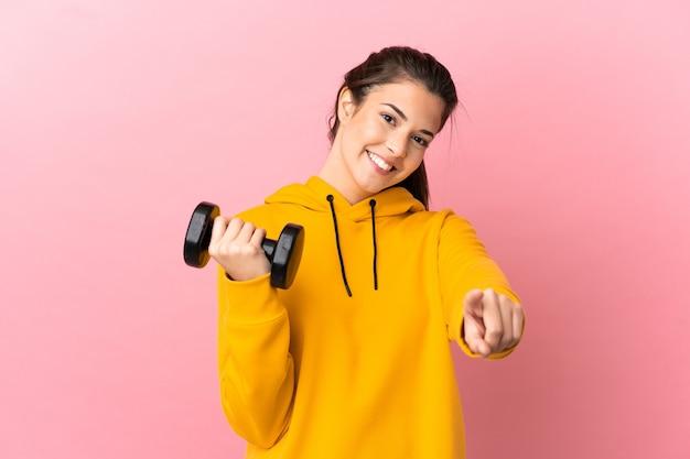 행복 한 표정으로 앞을 가리키는 격리 된 분홍색 배경 위에 역도를 만드는 젊은 스포츠 소녀