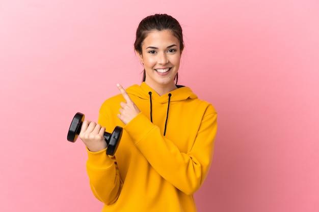 제품을 제시하기 위해 측면을 가리키는 격리 된 분홍색 배경 위에 역도를 만드는 젊은 스포츠 소녀
