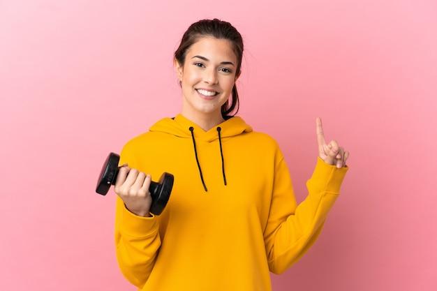 좋은 아이디어를 가리키는 격리 된 분홍색 배경 위에 역도를 만드는 젊은 스포츠 소녀