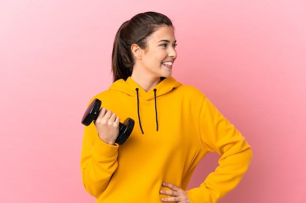 젊은 스포츠 소녀 엉덩이에 팔을 포즈와 미소 격리 된 분홍색 배경 위에 역도 만들기