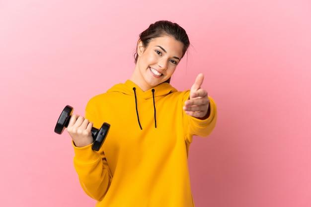 좋은 거래를 닫기 위해 악수하는 고립 된 분홍색 배경 위에 역도를 만드는 젊은 스포츠 소녀