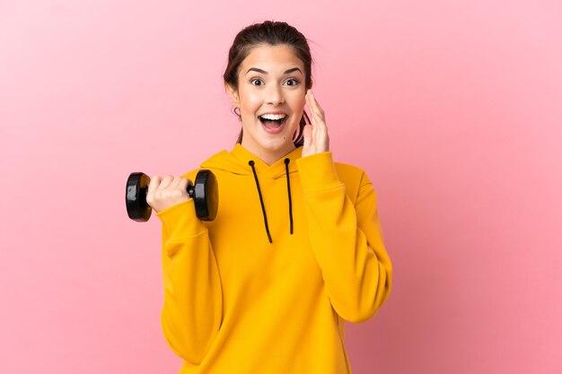 입 벌리고 외치는 격리 된 분홍색 배경 위에 역도를 만드는 젊은 스포츠 소녀