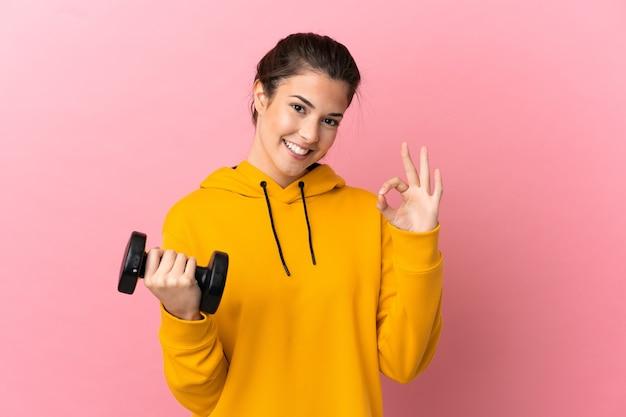 Молодая спортивная девушка делает тяжелую атлетику на изолированном розовом фоне, показывая пальцами знак ок
