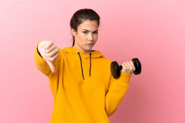 부정적인 표현으로 아래로 엄지 손가락을 보여주는 고립 된 분홍색 배경 위에 역도를 만드는 젊은 스포츠 소녀