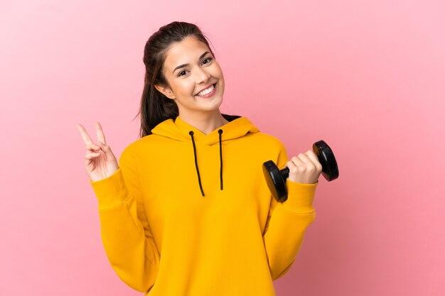 웃 고 승리 기호를 보여주는 고립 된 분홍색 배경 위에 역도를 만드는 젊은 스포츠 소녀