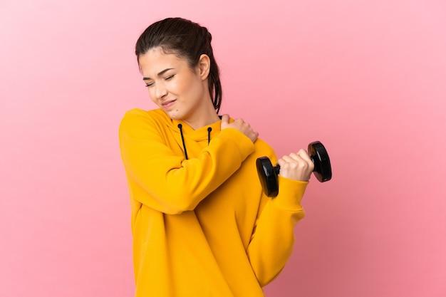 노력을 한 데 대한 어깨에 통증을 앓고 고립 된 분홍색 배경 위에 역도를 만드는 젊은 스포츠 소녀