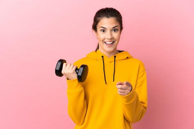 격리 된 분홍색 배경 위에 역도를 만드는 젊은 스포츠 소녀 놀라게 하 고 앞을 가리키는