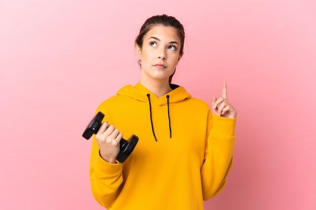 손가락을 가리키는 아이디어를 생각하는 격리 된 분홍색 배경 위에 역도를 만드는 젊은 스포츠 소녀