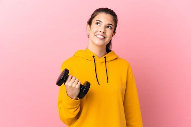 찾는 동안 아이디어를 생각 격리 된 분홍색 배경 위에 역도를 만드는 젊은 스포츠 소녀