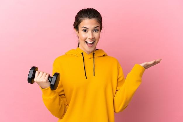 충격 된 표정으로 격리 된 분홍색 배경 위에 역도를 만드는 젊은 스포츠 소녀