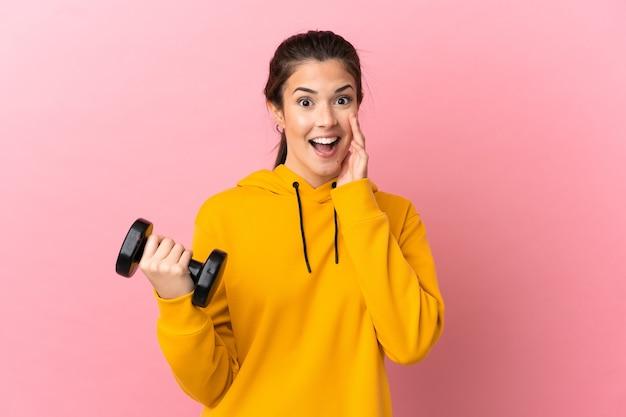 놀람과 충격 된 표정으로 격리 된 분홍색 배경 위에 역도를 만드는 젊은 스포츠 소녀