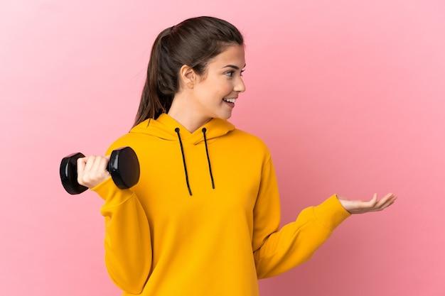 측면을 보는 동안 놀라운 표정으로 고립 된 분홍색 배경 위에 역도를 만드는 젊은 스포츠 소녀