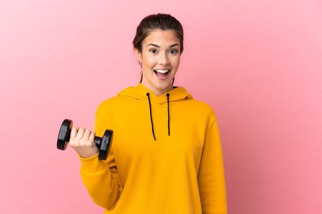 놀라운 표정으로 격리 된 분홍색 배경 위에 역도를 만드는 젊은 스포츠 소녀