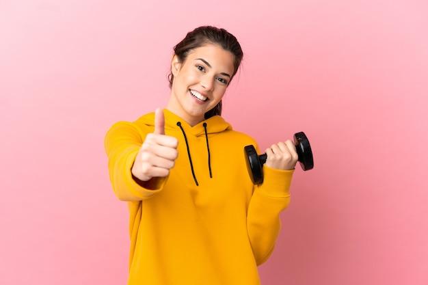 좋은 일이 일어났기 때문에 엄지 손가락으로 고립 된 분홍색 배경 위에 역도를 만드는 젊은 스포츠 소녀