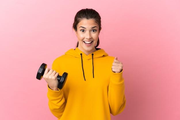 승자 위치에서 승리를 축하 격리 된 분홍색 벽 위에 역도를 만드는 젊은 스포츠 소녀