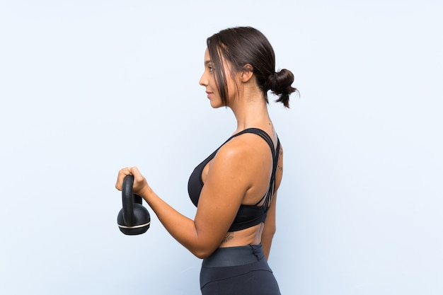 Young sport girl making weightlifting with kettlebell over isolated blue wall