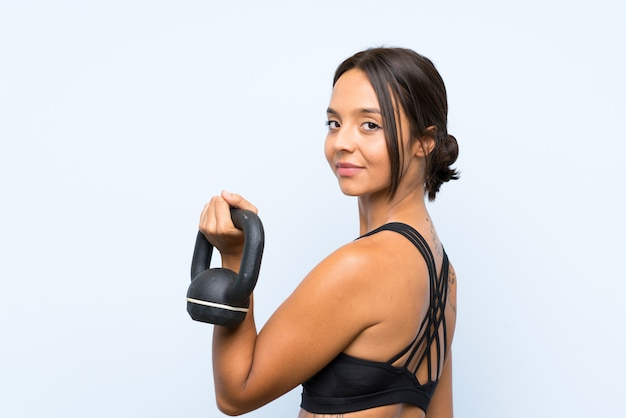 Young sport girl making weightlifting with kettlebell