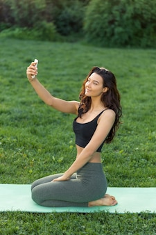 Young sport girl sit on yoga mat after doing yoga and making selfie on a smartphone outdoors on