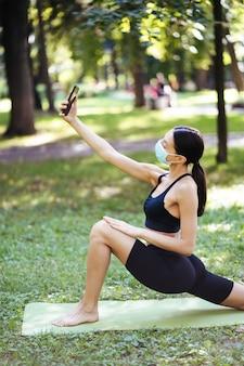 어린 스포츠 소녀 자연에 야외에서 스마트 폰에 selfie를 받아. 건강한 라이프 스타일 개념.