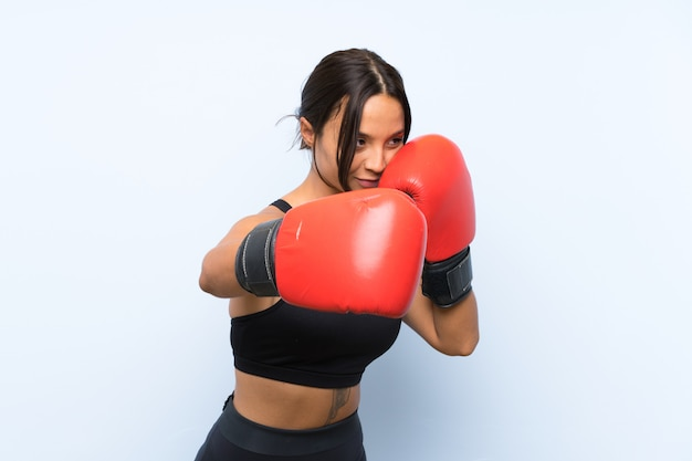 Young sport girl with boxing gloves over isolated blue background